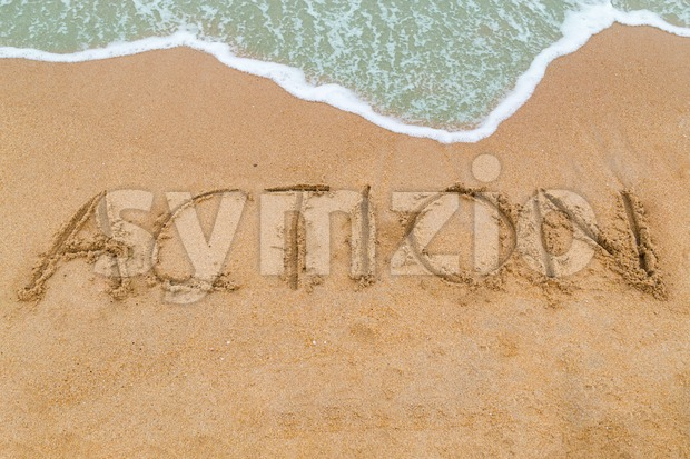 ACTION inscription written on sandy beach with wave approaching Stock Photo