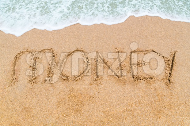 MONEY inscription written on sandy beach with wave approaching Stock Photo
