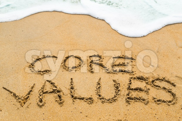CORE VALUES inscription written on sandy beach with wave approaching.