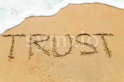 TRUST inscription written on sandy beach with wave approaching Stock Photo