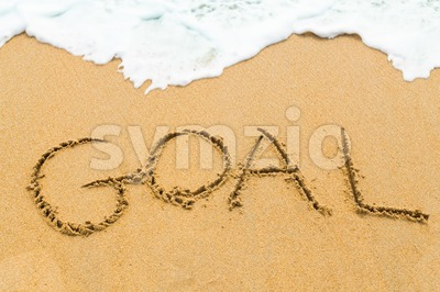 GOAL inscription written on sandy beach with wave approaching Stock Photo