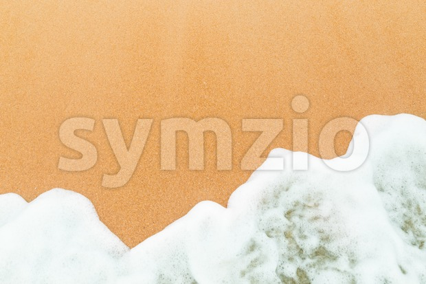 Calm sea waves breaking on sandy beach as background resources.