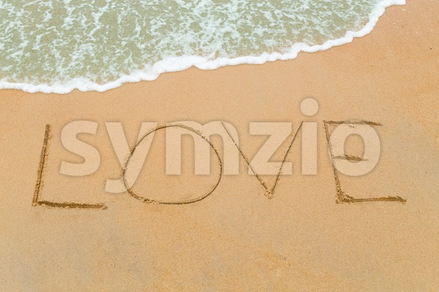 LOVE word drawn on serene sandy beach with soft blue wave approaching.
