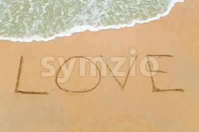 LOVE word drawn on sandy beach with wave approaching Stock Photo