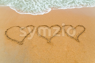 Three Hearts drawn on sandy beach with wave approaching Stock Photo