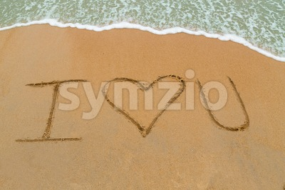 I Love You drawn on sandy beach with wave approaching Stock Photo