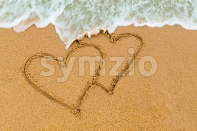 Twin double heart drawn on sandy beach with wave approaching Stock Photo