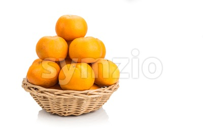 Stack of mandarin oranges in basket with white background Stock Photo