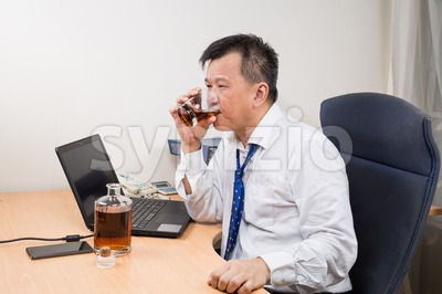 Frustrated and stressful Asian manager drinking hard liquor in office Stock Photo