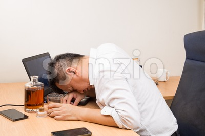Depressed Asian business manager drunk on office desk Stock Photo