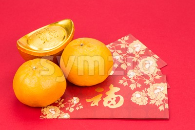 Mandarin oranges, gold nuggets, red packets, Chinese good luck character Stock Photo