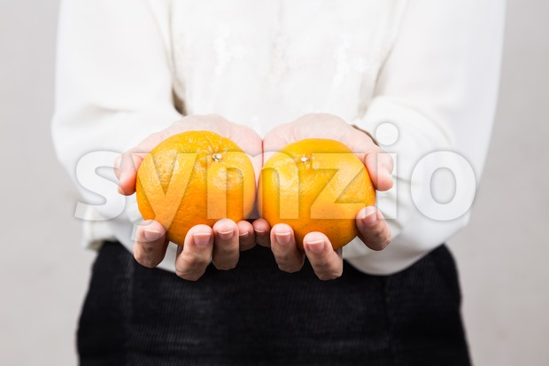 Perspective view woman giving mandarin oranges during Chinese New Year Stock Photo