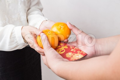 Woman giving mandarin oranges, red envelop with Good Luck character Stock Photo