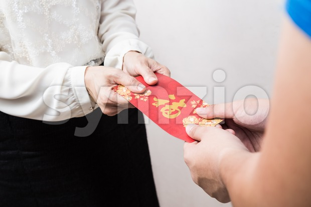 Woman giving red envelop with Good Luck character in Chinese Stock Photo