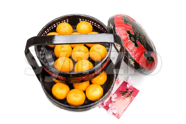 Juicy mandarin oranges in traditional basket carrier with Good Luck Chinese character on red packets in white background