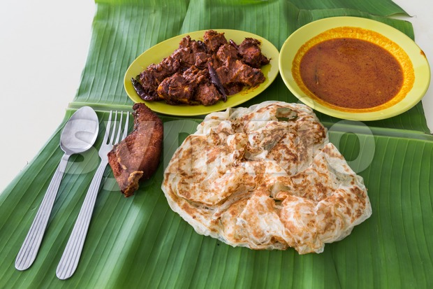 Roti prata on banana leaf with masala mutton, fish, curry Stock Photo