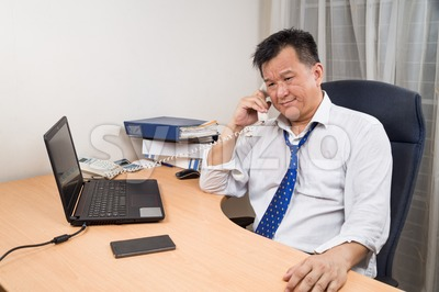 Stressful and frustrated Asian manager talking on telephone in office Stock Photo