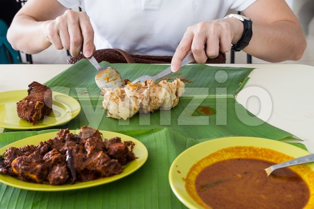 Person eating roti prata or roti canai served on banana leaf, with masala mutton, fried fish and curry
