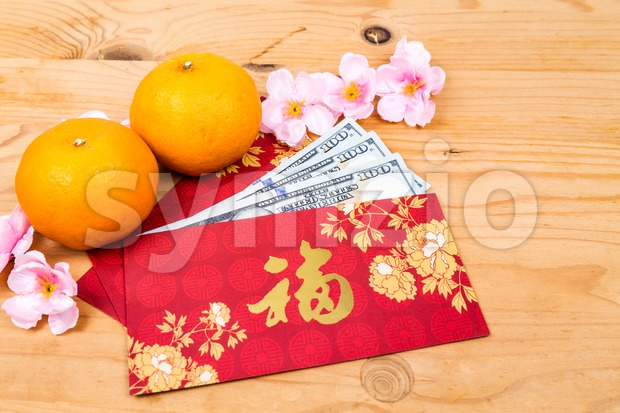 Red packet with Good Fortune character contains US Dollar notes Stock Photo