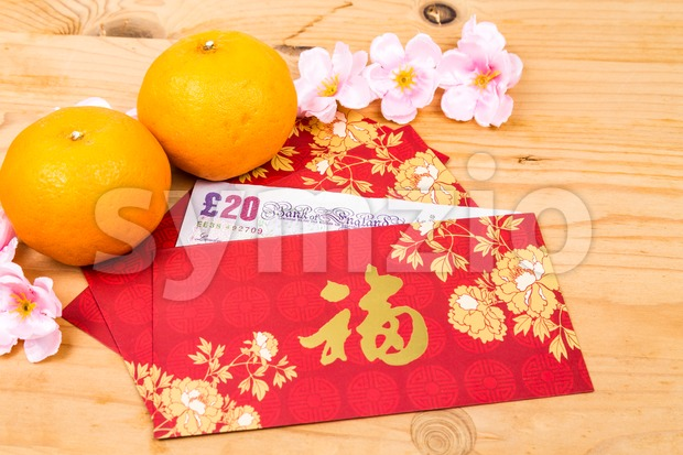 Red packet with Good Fortune character contains Sterling Pound  currency Stock Photo