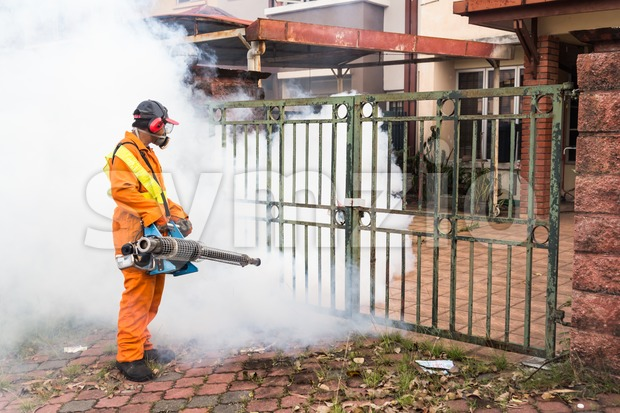Worker fogging residential area with insecticides to kill aedes mosquito Stock Photo