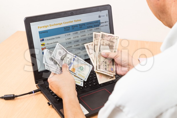 Hand sorting US Dollar and Japanese Yen currency Stock Photo