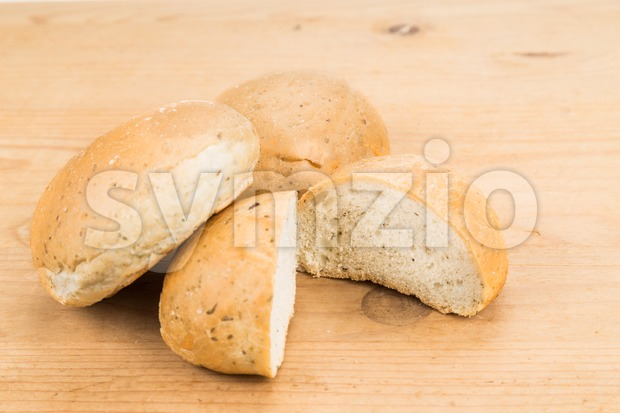Freshly baked healthy gluten-free delicious wholemeal buns with herbs on wooden surface