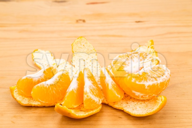 Peeled organic sweet and juicy mandarin oranges on wooden surface