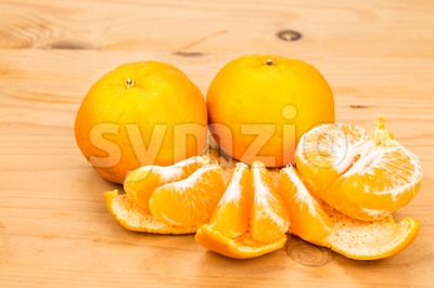 Peeled sweet and juicy mandarin oranges on wooden surface Stock Photo
