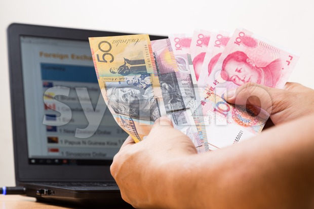 Hand sorting Australian Dollar and China Yuan in front of currency exchange chart on computer screen.