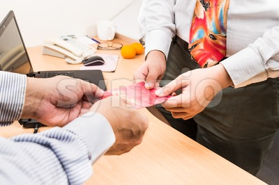 Employee receiving red packet with Good Fortune wordings, from employer Stock Photo