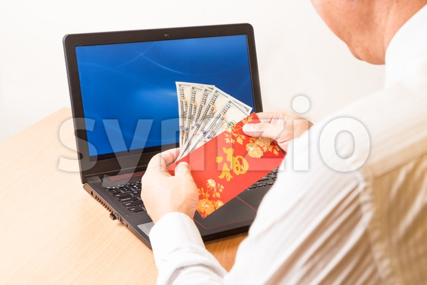 Employee displaying red packet with Good Fortune character in office Stock Photo