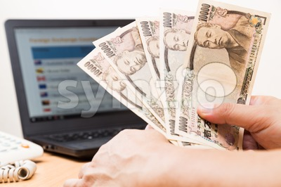 Hand holding Japanese Yen in office with computer in background Stock Photo