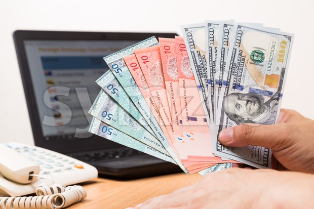 Hand sorting Malaysia Ringgit and US Dollar with computer background Stock Photo