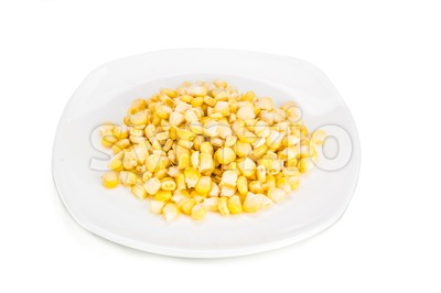 Fresh maize corn kernels on plate against white background Stock Photo
