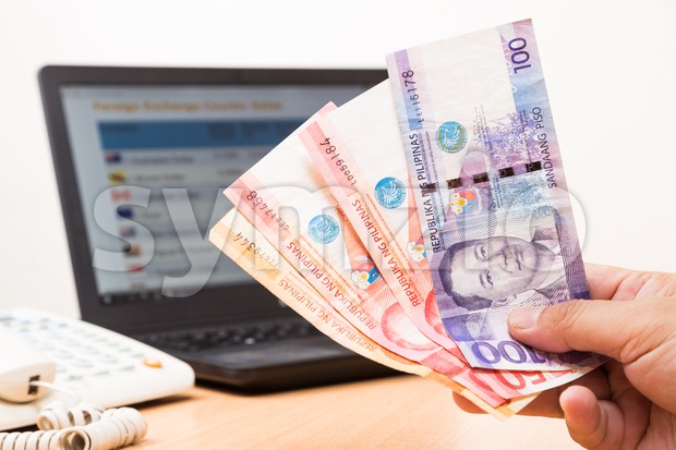 Hand holding Philippines Piso currency in office with computer screen showing foreign exchange table in background