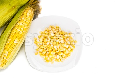 Overhead view fresh maize corn cob and kernels on plate Stock Photo