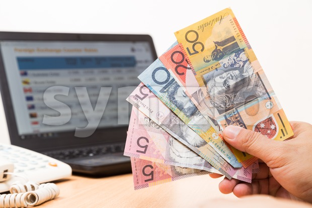Hand holding Australian dollar in office with computer screen showing foreign exchange table in background