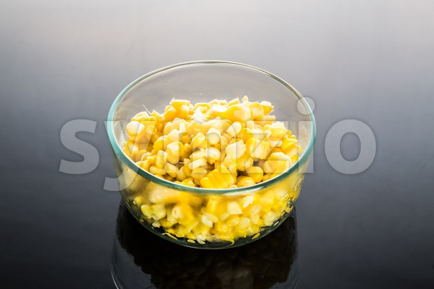 Fresh organic corn kernels in transparent glass bowl in dark background