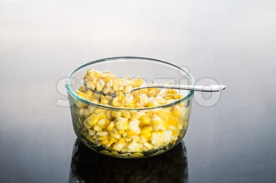 Corn kernels in transparent glass bowl  in dark reflective background Stock Photo
