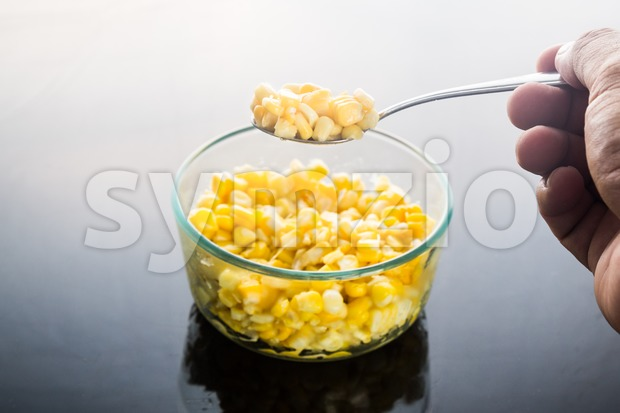 Selective focus on spoonful of corn kernels against dark background Stock Photo