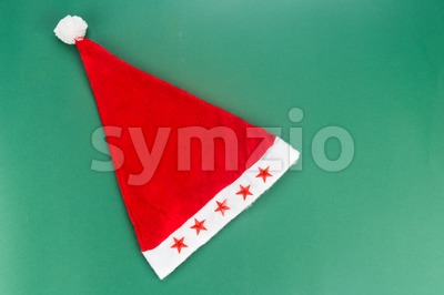 Beautiful red Christmas hat on green background. Stock Photo
