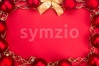 Beautiful ornaments framed Christmas decoration in red background. Stock Photo