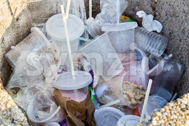 Environmental unfriendly non-biodegradable PVC containers and straws in rubbish bin Stock Photo