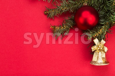 Simple red Christmas background with fir tree,  ornaments and bell. Stock Photo