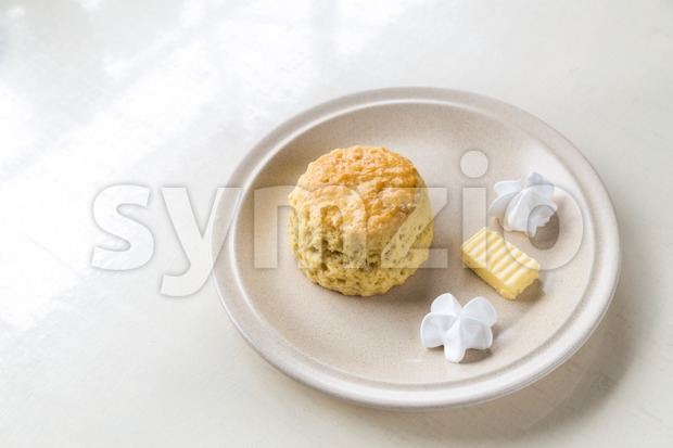Simple and delicious English scones set with butter and cream with ambient light