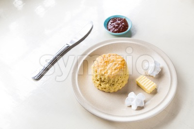 Simple English scones set with butter, cream and strawberry jam Stock Photo