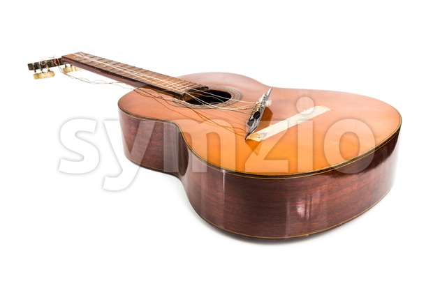 Broken classical guitar with detached bridge isolated in white background Stock Photo