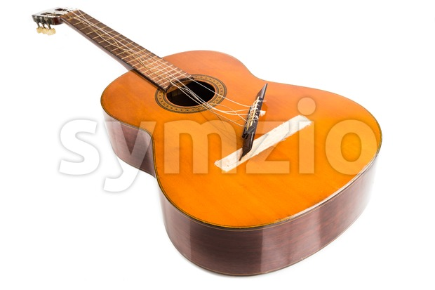 Broken brown classical guitar with detached bridge from body isolated in white background