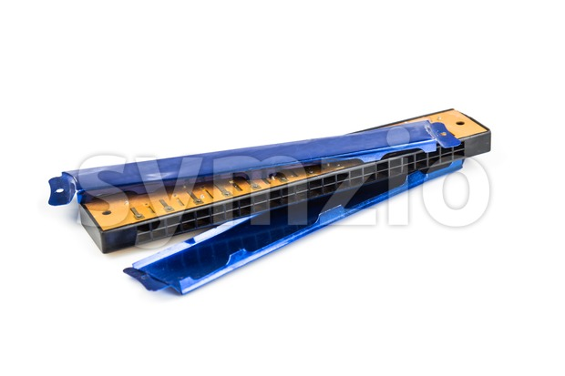 Broken harmonica with  detached cover plated isolated in white background